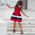 Vestido sem mangas para menina. Modelo com pinças. Elementos decorativos: fita decorativa de cor a contraste na cintura. Motivo de riscas.